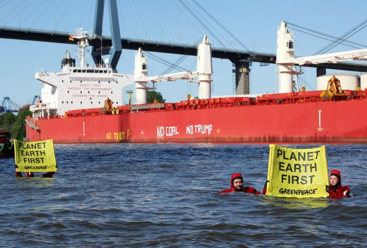"In this June 1, 2017 photo Greenpeace activists demonstrate in front of the freighter ""SBI'Subaru"" holding a banner with the inscription ""Planet Earth First""' in Hamburg, Germany."