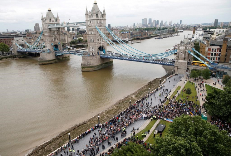 People attend a vigil for victims of Saturday's attack on London Bridge, at Potter's Field Park with Tower Bridge in the background in London, Monday, June 5, 2017.