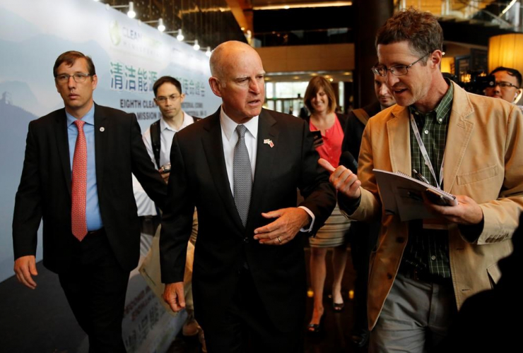 California Gov. Jerry Brown, center, talks with reporters after delivering a speech during the Clean Energy Ministerial International Forum on Electric Vehicle Pilot Cities and Industrial Development, at a hotel in Beijing, on June 6, 2017.
