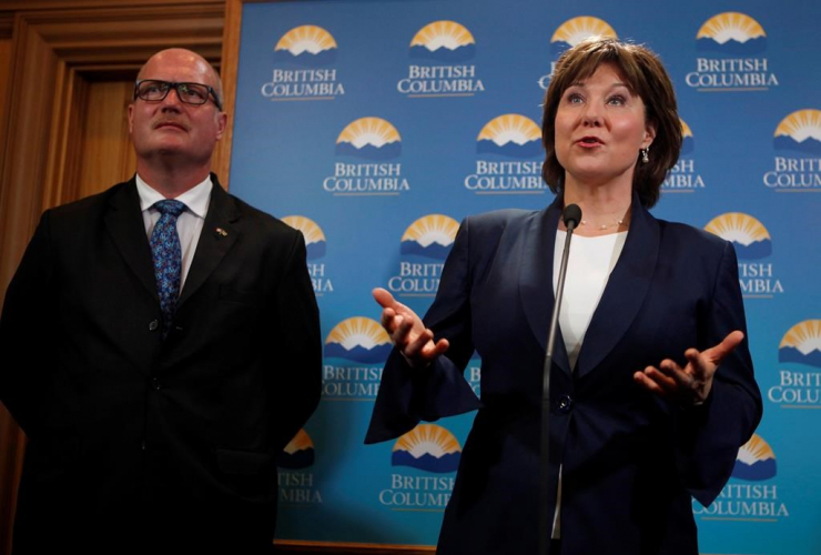 B.C. Finance Minister Michael de Jong joins Premier Christy Clark to talk with media after being sworn-in as Premier following a ceremony at Legislature in Victoria, B.C., on Thursday, June 8, 2017.