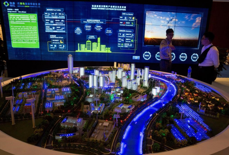 In this photo taken Wednesday, June 7, 2017, visitors look at a model of a city run on clean energy during an international clean energy conference held in Beijing, China.