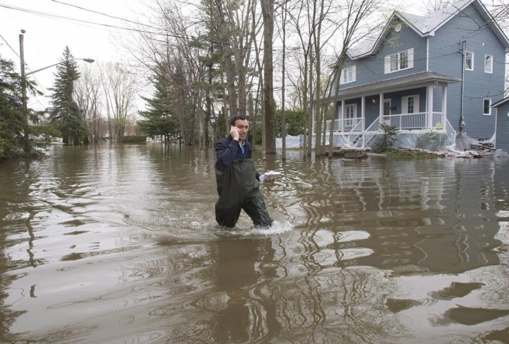 A man makes his way through the flooded streets in Laval, Que., on Wednesday, May 10, 2017.