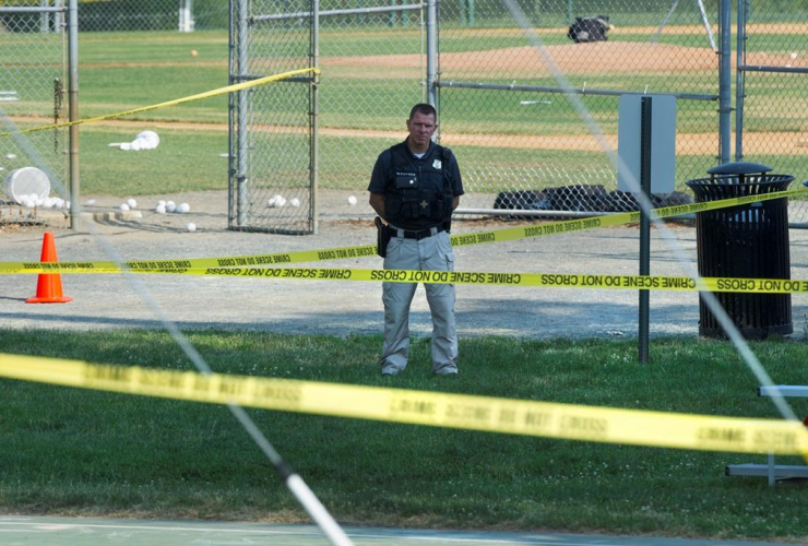 A police officer stands watch behind police tape near strewn softballs on a field in Alexandria, Va., on Wednesday, June 14, 2017, after a multiple shooting involving House Majority Whip Steve Scalise of La.