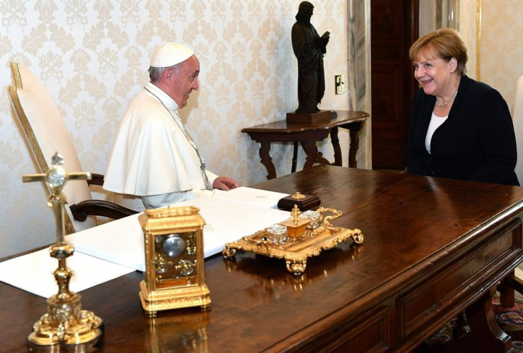 Pope Francis sits at a table with German Chancellor Angela Merkel on the occasion of their private audience, at the Vatican City, on Saturday, June 17, 2017.