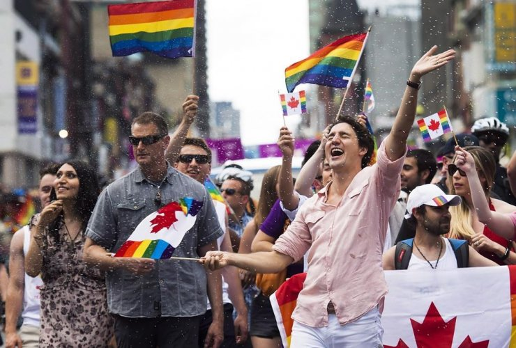 Prime Minister Justin Trudeau is splashed with water as he waves a flag at the annual Pride Parade in Toronto on Sunday, July 3, 2016. File photo by The Canadian Press/Nathan Denette