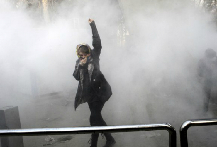 An Iranian protester raises her fist above her head.