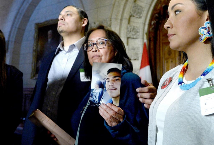 Debbie Baptiste holds up a photo of her son Colten Boushie, as the family spoke to reporters in the Foyer of the House of Commons after a day of meetings on Parliament Hill, in Ottawa on Tuesday, Feb. 13, 2018. THE CANADIAN PRESS/Justin Tang