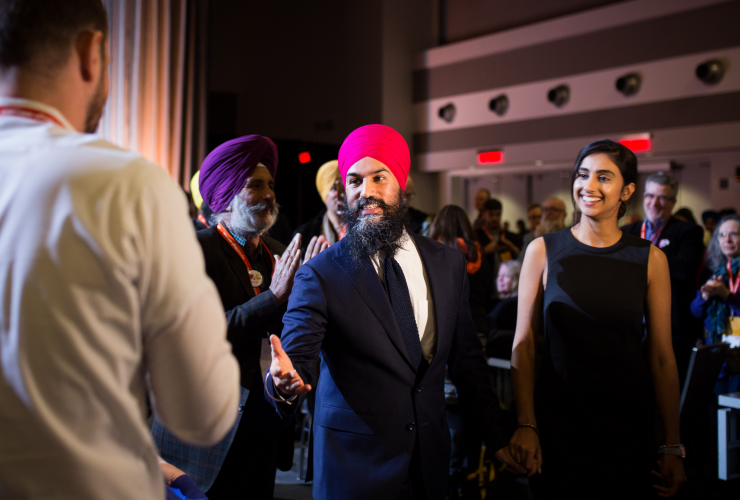 Jagmeet Singh reaches out to delegates as he leaves the NDP convention stage with his fiancée Gurkiran Kaur on Feb. 17, 2018 in Ottawa. Photo by Alex Tétreault