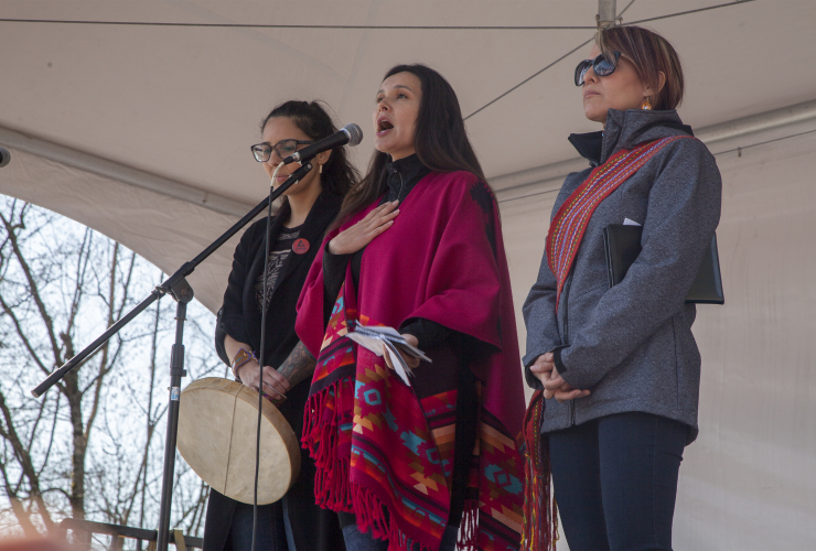 Melina Laboucan Massimo (centre) speaks at the Protect the Inlet rally on Burnaby Mountain in B.C. on March 10, 2018. She is accompanied by Eriel Tchekwie (left) and Jesse Cardinal (right). Photo by Trevor Mack