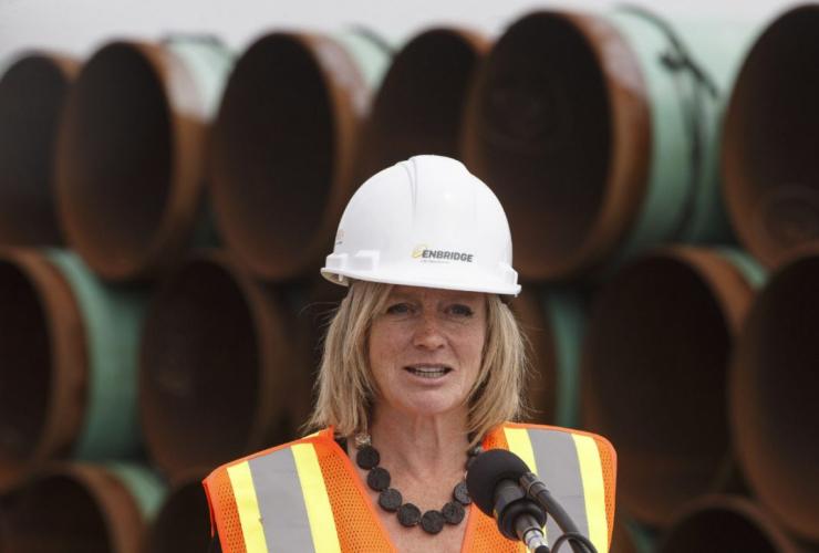 Alberta Premier Notley wearing an Enbridge cap.