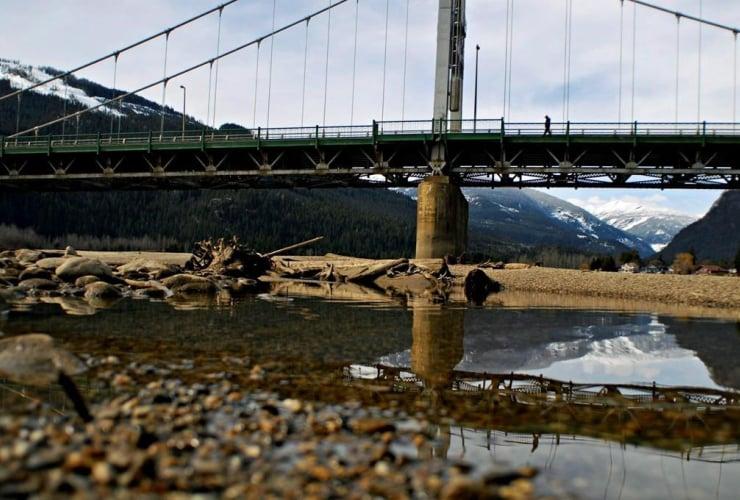 man, crosses, bridge, Columbia River, Revelstoke,