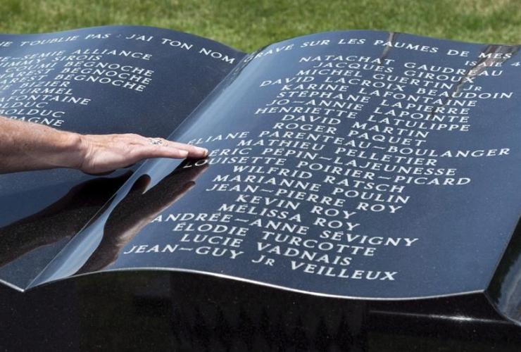 man, touches, stone monumen, Ste-Agnes church, memorial service, Lac-Megantic,