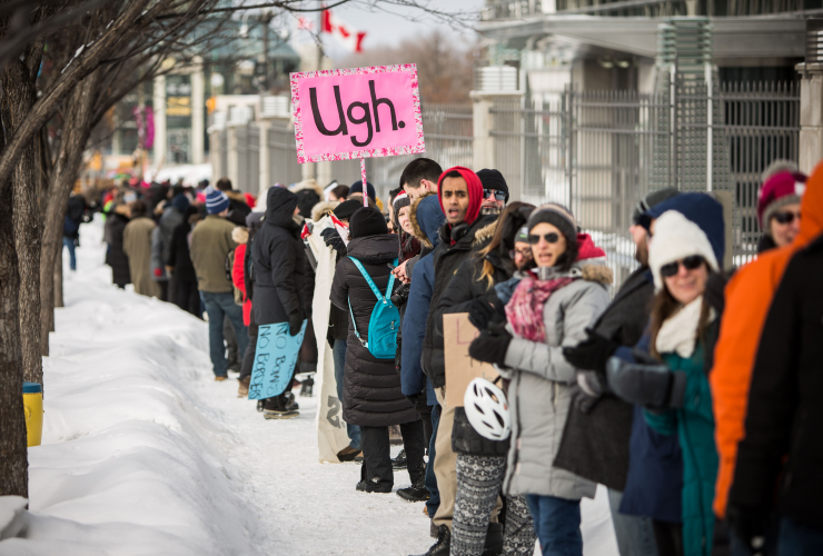 Protesters line up in front of the U.S. embassy and demand that President Trump remove his travel ban on seven Muslim-majority countries, Mon. Jan. 30, 2017 in Ottawa. Photo by Alex Tétreault