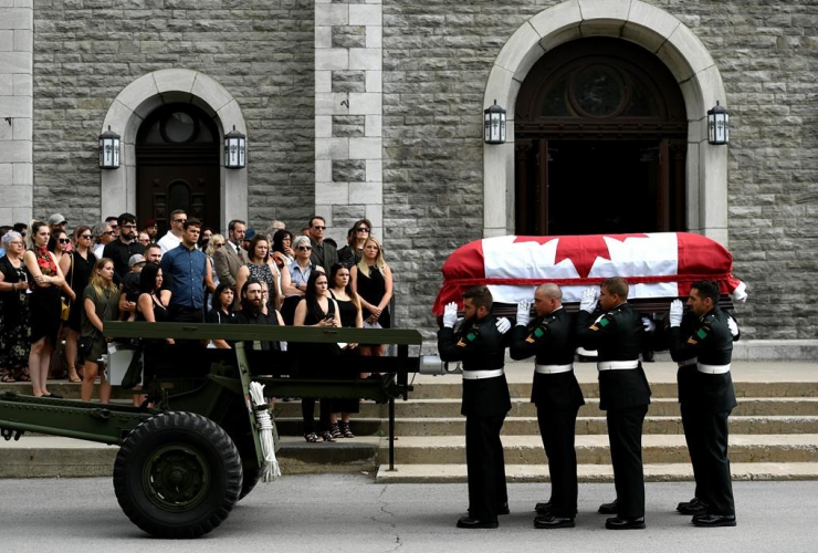Mourners stand on the steps of the Paroisse Saint-Gregoire-de-Nazianze as the casket of Bombardier Patrick Labrie is carried inside on July 6, 2019. File photo by The Canadian Press