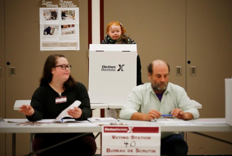 Two-year-old Juniper Martens, voting booth, baby carrier, mother Melissa, Manitobans, election day,