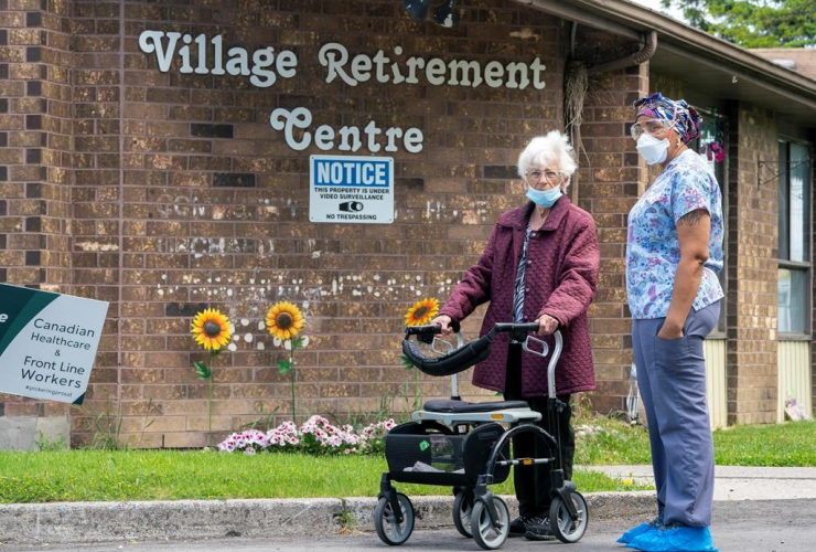 A resident and a worker watch as 150 nursing union members show support at rchard Villa Long-Term Care in Pickering, Ontario on Monday, June 1, 2020. Photo by The Canadian Press/Frank Gunn
