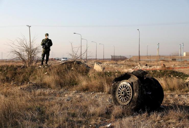 police officer, guard, debris, Ukrainian plane, crashed, Shahedshahr, Tehran, Iran,
