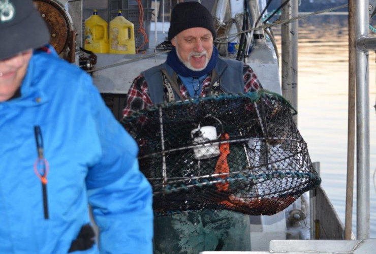 Guy Johnson carrying a prawn trap on a boat deck.