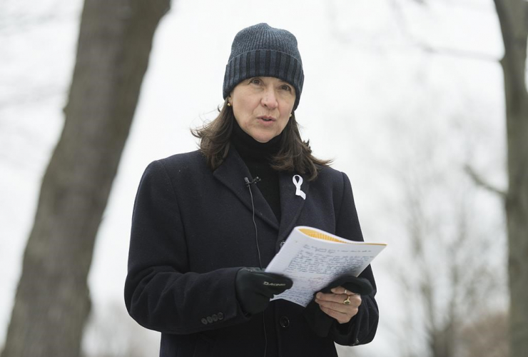 A woman wearing a toque and an overcoat stands outside, reciting a poem from a notebook