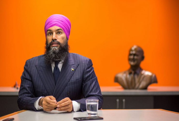 A man in a suit and turban sits in front of a bright orange wall
