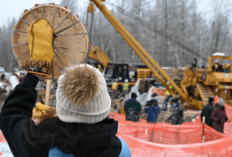 A person in a toque holds a drum next to a construction site