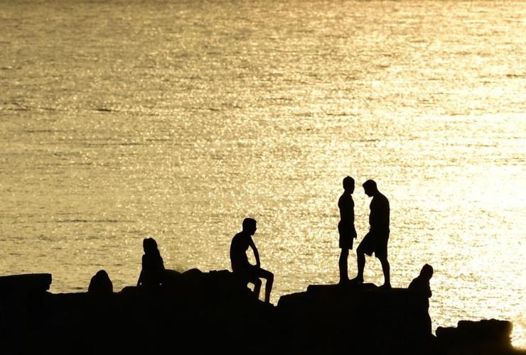 People, rocks, beach, Kavouri, Athens, Greece,