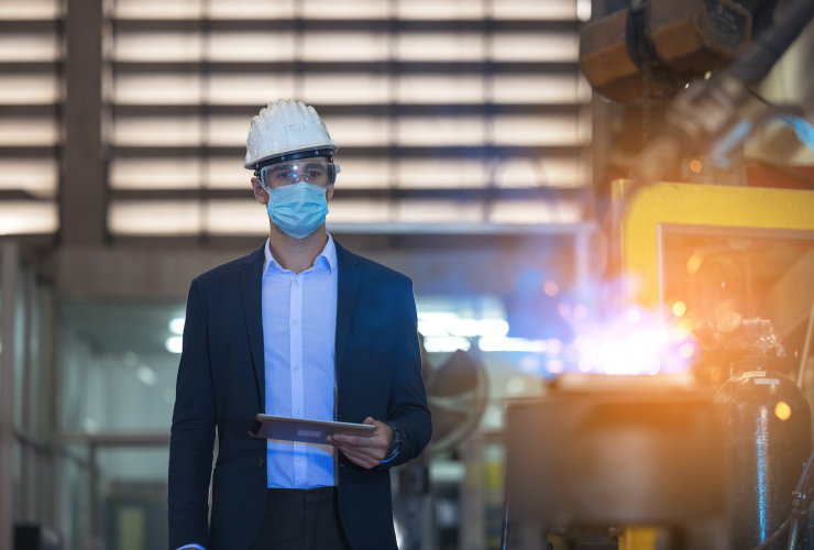An engineer wearing a hard hat, mask, and safety glasses watching sparks fly